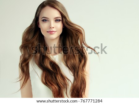 Brunette  girl with long  and   shiny curly hair .  Beautiful  model woman  with wavy hairstyle. Care and beauty