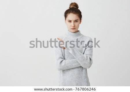 Serious demanding woman pointing index finger to side. Young strict female teacher gesturing frowning paying attention while having class over white background. Human emotions concept Royalty-Free Stock Photo #767806246