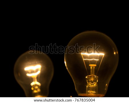 Yellow light bulb on black background #767835004