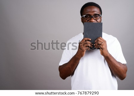 Studio shot of young African man wearing white shirt and eyeglasses against gray background #767879290