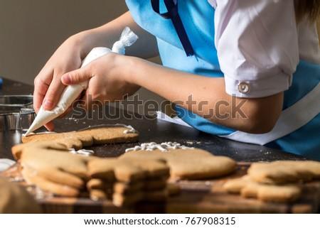 kids hand decorating cookies with sugar. Making Gingerbread Cookies Series #767908315