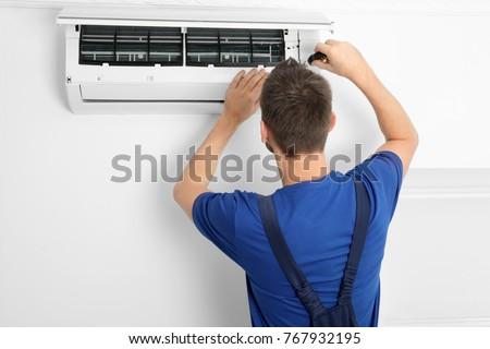 Male technician repairing air conditioner indoors #767932195