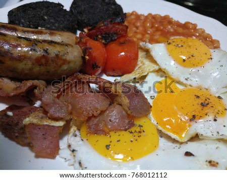 juicy hot sausages and bacon with eggs tomatoes baked beans and black pudding #768012112