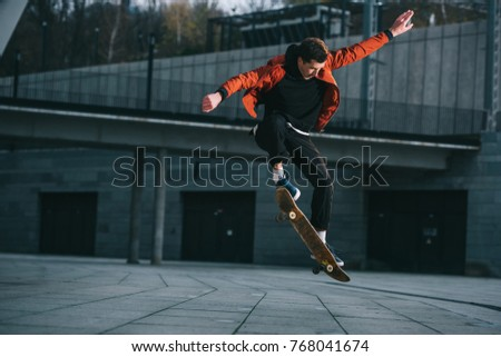 skateboarder doing jump trick in urban location #768041674