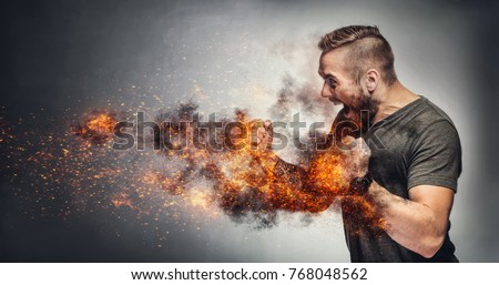 Excited man in fighting gesture with fists on fire. Rage concept. Heated fight. Aggressive behaviour concept Royalty-Free Stock Photo #768048562