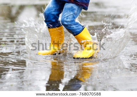 Close-up of kid wearing yellow rain boots and walking during sleet, rain and snow on cold day. Child in colorful fashion casual clothes jumping in a puddle. Having fun outdoors. #768070588