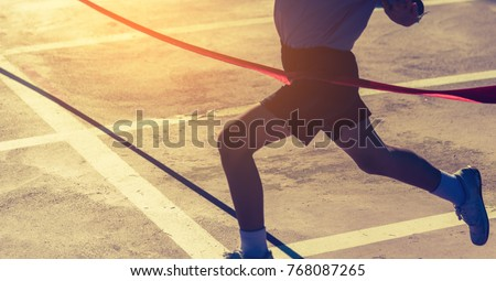 silhouette image of ribbon at finish line with kids winner crossing it.(focus on ribbon)) #768087265