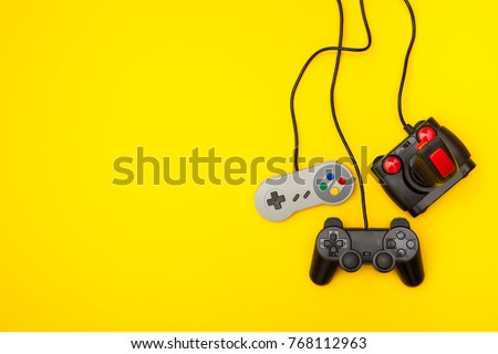 Retro computer gaming controllers on a bright yellow background #768112963