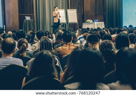Abstract blurred photo of conference hall or seminar room with attendee background #768120247
