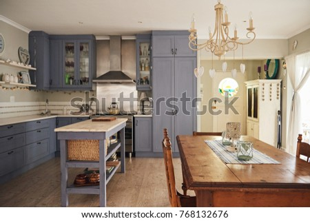 Interior of a country style kitchen with an island, dining table and modern appliances in a residental home #768132676