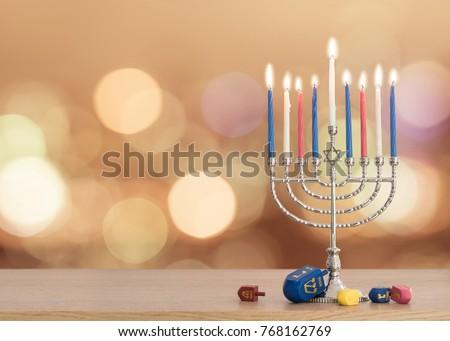 Hanukkah/ Chanukah Jewish holiday background with Hanukah/ Chanukkah menorah (Judaism candelabra) burning candles and traditional Dreidel game toy on wood table and on autumn light bokeh sun flare