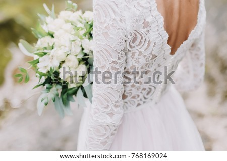 Bride holds a wedding bouquet, wedding dress, wedding details #768169024