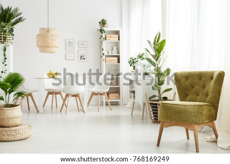 Green velvet armchair standing in the corner of bright dining room interior with windows #768169249