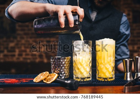 Close up details of working bartender. Pouring citrus cocktail over ice, orange cocktail details #768189445