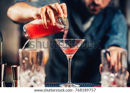 Close up details of barman pouring vodka cosmopolitan cocktail in martini glass #768189757