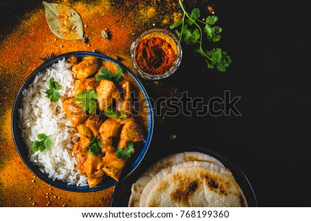 Indian Butter chicken with basmati rice in bowl, spices, naan bread. Black background. Space for text. Butter chicken, traditional Indian dish. Top view. Chicken tikka masala. Indian cuisine  #768199360