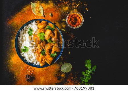 Indian Butter chicken with basmati rice in bowl, spices, black background. Space for text. Butter chicken, traditional Indian dish. Top view. Chicken tikka masala. Indian cuisine concept. Overhead #768199381