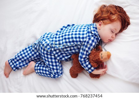 adorable redhead toddler baby sleeping with plush toy in flannel pajamas #768237454