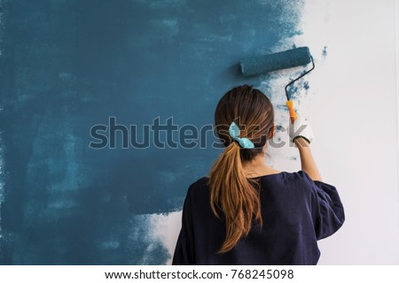 Young asian happy woman painting interior wall with paint roller in new house, Home decoration concept Royalty-Free Stock Photo #768245098