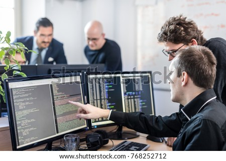 Startup business and entrepreneurship problem solving. Young AI programmers and IT software developers team brainstorming and programming on desktop computer in startup company share office space. #768252712