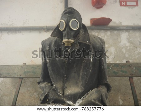 """Bondeno, Italy - December 2, 2017. Art installation """"The silent scream of Chernobyl"""". Underground with smoke. Reconstruction of the disaster.  Mannequin with gas mask and overcoat. #768257776"""