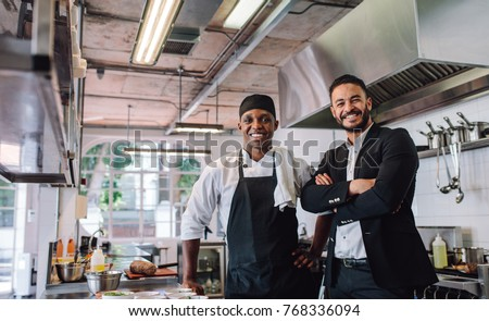 Portrait of restaurant owner with chef in kitchen. Businessman with professional cook standing together and looking at camera. #768336094