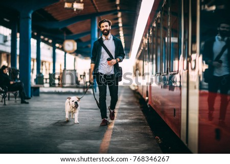 Young man going on vacation with train. Handsome guy walkiing with his bulldog at train station. Royalty-Free Stock Photo #768346267