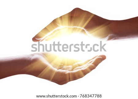 Woman hands protecting and containing bright, glowing, radiant, shining light. Emitting rays or beams expanding of center. Religion, divine, heavenly, celestial concept. White background copy space Royalty-Free Stock Photo #768347788