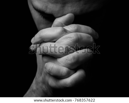 Close up of faithful mature man praying, hands folded in worship to god with head down and eyes closed in religious fervor. Black background. Concept for religion, faith, prayer and spirituality. #768357622