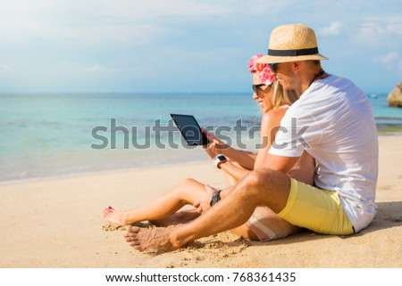Couple using tablet on the beach
