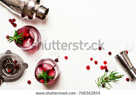 Red cranberry cocktail with ice, rosemary and vodka, bar tools, white background, top view #768362854