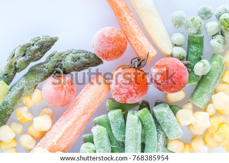 frozen vegetables: cherry tomatoes. asparagus, corn, baby carrot, french beans, peas  on white cutting board, top view, macro Royalty-Free Stock Photo #768385954