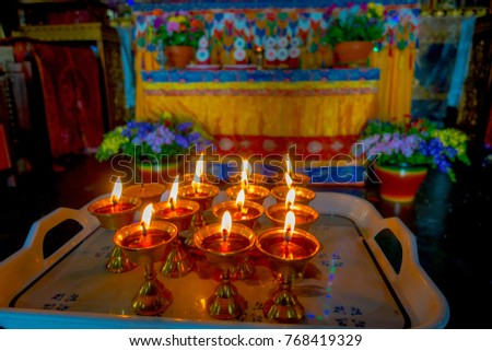 POKHARA, NEPAL - OCTOBER 06 2017: Close up of some candels inside of a goblet over a plastic tray in Thrangu Tashi Choling Monastery in Kathmandu, Nepal #768419329