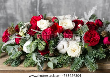 Winter decor. The composition of the branches Nobilis and fresh flowers. Work florist in shop. For decorating a family dinner #768429304