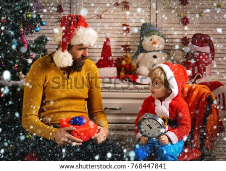 new year christmas snow concept New year man and small boy with clock. Xmas party celebration, fathers day. Winter holiday and boxing day. Christmas happy child and father with present box. Santa kid #768447841
