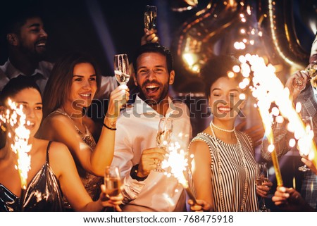 Cropped shot of young friends holding sparklers at a party Royalty-Free Stock Photo #768475918