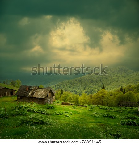 Mystery mountain landscape. Ray of light in dark clouds over the old wooden shack in green valley #76851145