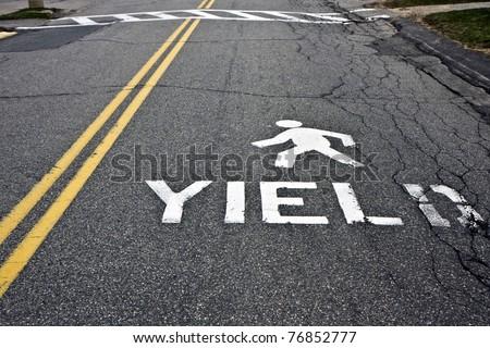 Warning at crossroad saying yield and person sign on asphalt