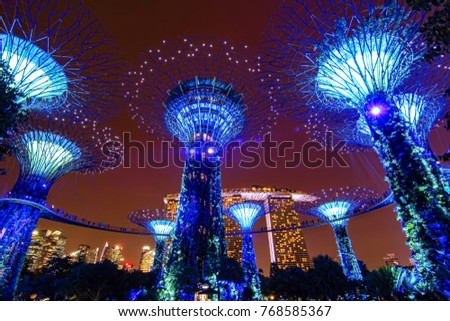 SINGAPORE - OCTOBER 16, 2017: Gardens by the Bay in Singapore. Beauty giant trees landmark in the Singapore Park at night turns into a glowing colored lights is main Marina Bay Sands district tourist  #768585367
