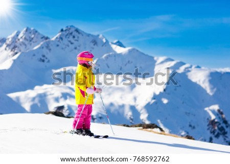 Child skiing in mountains. Active toddler kid with safety helmet, goggles and poles. Ski race for young children. Winter sport for family. Kids ski lesson in alpine school. Little skier racing in snow #768592762