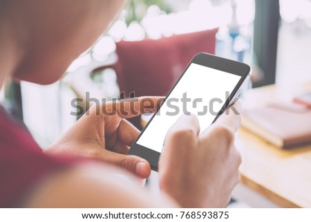Woman relaxing while using smartphone blank screen for graphics display montage. Over the shoulder view of #768593875