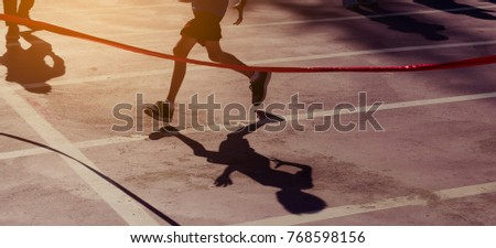 silhouette image of ribbon at finish line with kids winner crossing it.(vintahe tone) #768598156