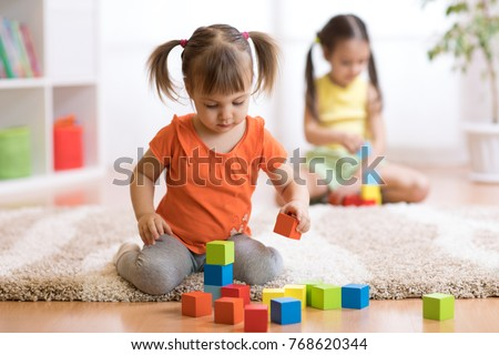 Children toddlers girls play toys at home, kindergarten or nursery. Royalty-Free Stock Photo #768620344