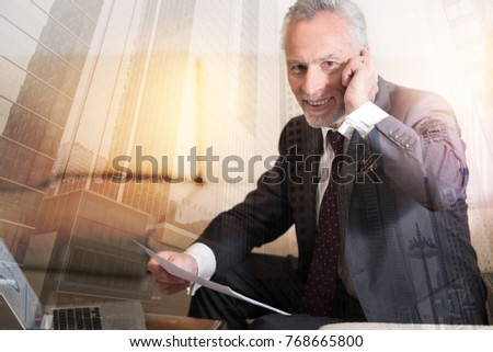 Positivity is the key to success. Cheerful man looking into the camera with a smile on his face while working with business documents and enjoying phone conversation. #768665800