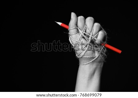 Hand with red pencil tied with rope, depicting the idea of freedom of the press or freedom of expression on dark background in low key. international human rights day concept. #768699079
