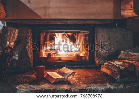 Open book by the Fireplace with Christmas ornaments. Open storybook lying on a wooden bench by the fireside. Cozy relaxed magical atmosphere in a chalet house decorated for Christmas. Holiday concept.