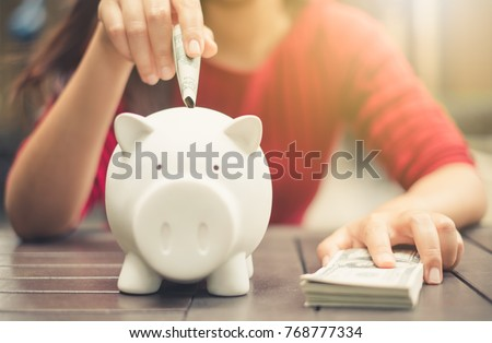 woman hand putting money bank note dollar into piggy for saving money wealth and financial concept. #768777334