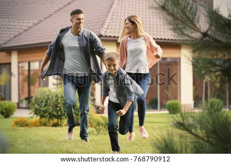 Happy family playing in courtyard near their house #768790912