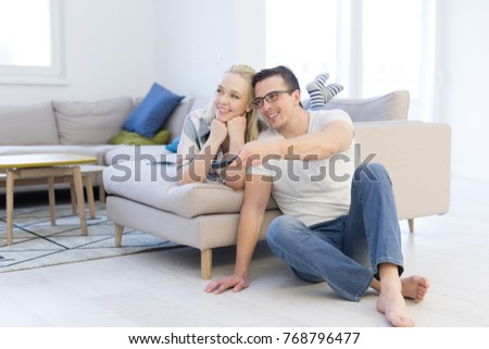 Young couple on the sofa watching television together in their luxury home #768796477