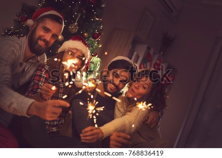Group of young friends having fun at a New Year's celebration, holding sparklers at a midnight countdown. Focus on the guy on the right #768836419